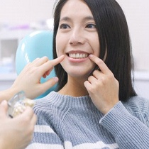 A woman pointing at her smile in a dental office.