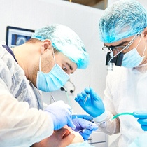 dentist performing dental implant surgery