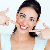 A woman pointing at her smile.