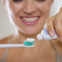 A woman applying toothpaste to a toothbrush.