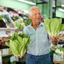 elderly man buying vegetables at the grocery store