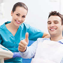 Smiling man in dental chair giving thumbs up