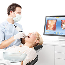 Dentist looking at digital impression of patient's teeth