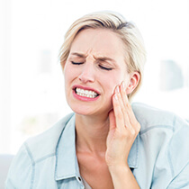 Astoria Emergency Dentist lady in pain holding cheek