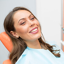 Lady laying in dental chair smiling