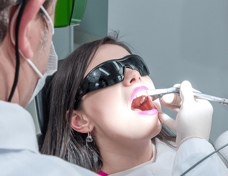 Dr. Shkurti shining light into patient's mouth