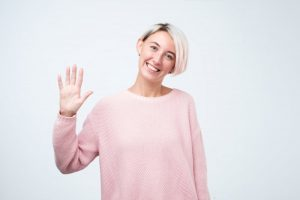 Smiling woman waving to her Astoria dentist in COVID-19