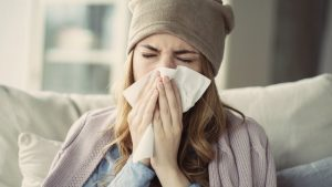woman blowing her nose during cold and flu season in Astoria