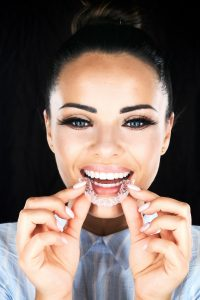 Woman wearing a light blue shirt smiling and holding an Invisalign tray near her mouth
