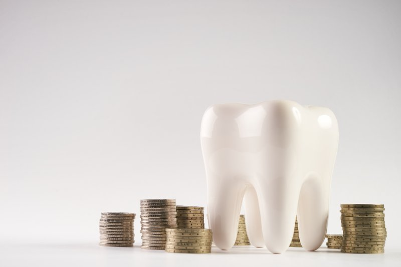 Model of a tooth surrounded by stacks of coins