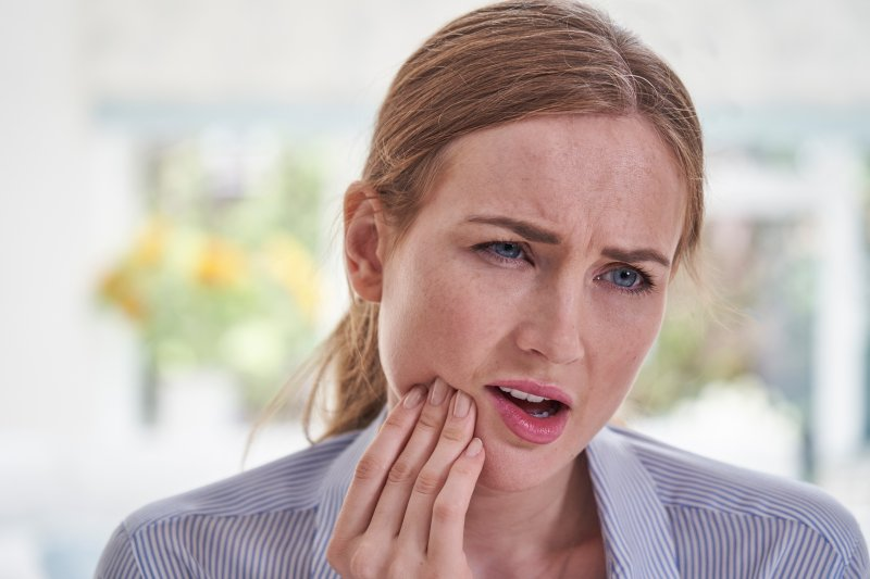 Woman with dental implants rubbing her jaw in concern